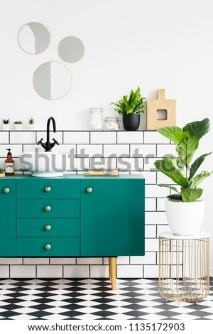 Green cabinet next to plant on gold table in modern bathroom interior with mirrors. Real photo #1135172903
