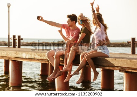 Picture of group of friends sitting outdoors on the beach take a selfie.