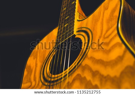 A wooden acoustic guitar is photographed in the dark