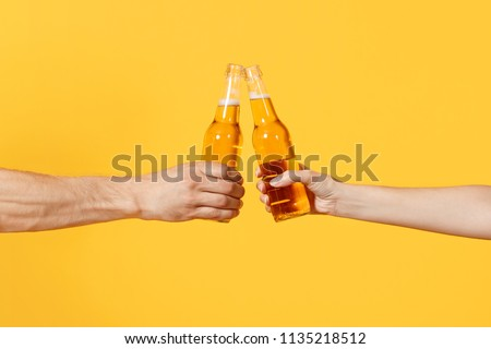 Close up cropped of woman and man two hands horizontal holding lager beer glass bottles and clinking isolated on yellow background. Sport fans cheer up. Friends leisure lifestyle concept. Copy space #1135218512