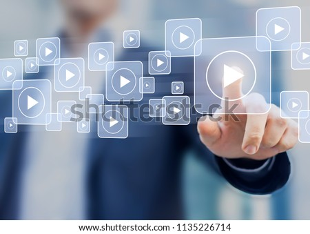 Video on demand technology with person touching play button on virtual screen to watch online VOD streaming of movie or TV #1135226714