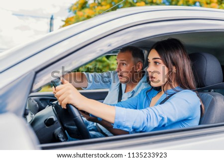 Woman Driver - Car Accident, yells in fear or frustration. Student girl sitting scared in a car. incident happens. Car Crash Accident with a Scared Driver and a instructor #1135233923