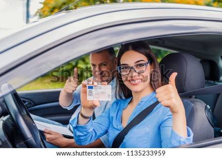 Driving school. Beautiful young woman successfully passed driving school test. She looking sitting in car, looking at camera and holding driving license in hand. Girl with driving license  #1135233959