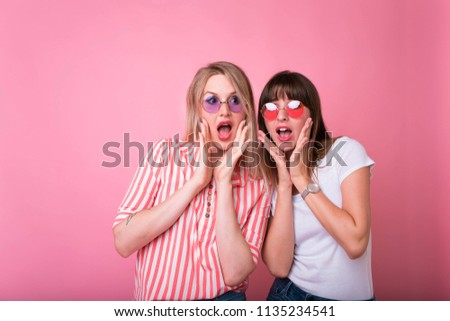 Two cheerful excited young women shouting over pink background.Studio shot of two scared Caucasian female student. raising brows and keeping hands on faces #1135234541