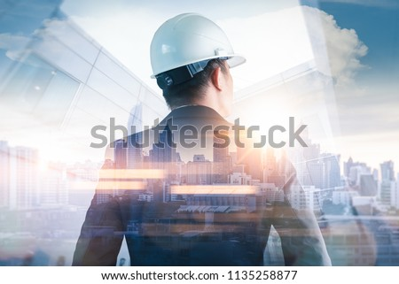 The double exposure image of the engineer standing back during sunrise overlay with cityscape image. The concept of engineering, construction, city life and future. #1135258877