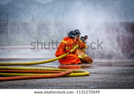Fireman using water and extinguisher to fighting with fire flame in an emergency situation Car crash .under danger situation all firemen wearing suit for safety.