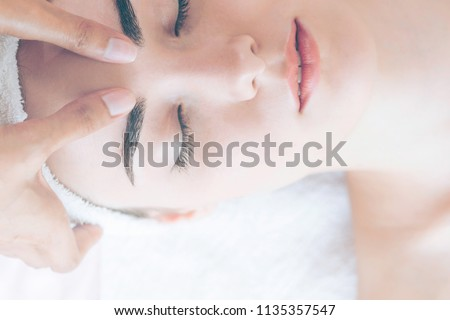 Relaxed woman lying on spa bed for facial and head massage. Concept of beauty and facial treatment. #1135357547