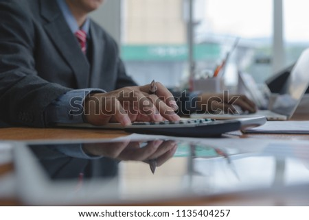 Businessman or accountant working on desk and using calculator to calculate business data, accountancy document and laptop computer in office, Business concept. #1135404257