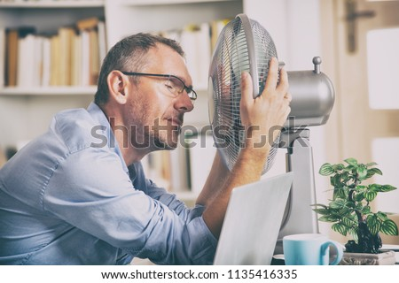 Man suffers from heat while working in the office and tries to cool off by the fan Royalty-Free Stock Photo #1135416335