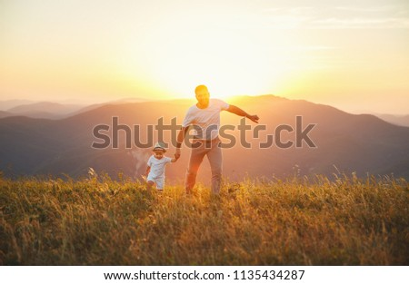 Father's day. Happy family father and toddler son playing and laughing on nature at sunset #1135434287
