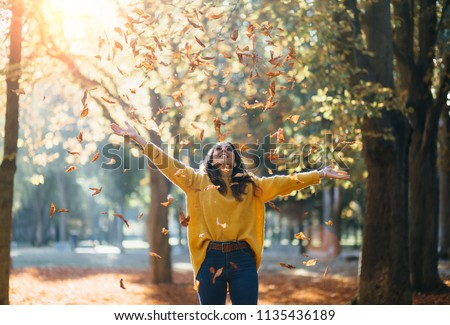 Casual joyful woman having fun throwing leaves in autumn at city park. Royalty-Free Stock Photo #1135436189