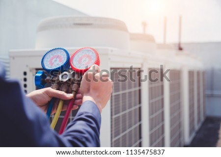 Technician is checking air conditioner ,measuring equipment for filling air conditioners. #1135475837