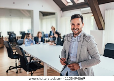 Portrait of successful entrepreneur, colleagues working in the background. Royalty-Free Stock Photo #1135494569