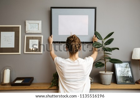 Girl hanging a frame on a gray wall, sun light Royalty-Free Stock Photo #1135516196