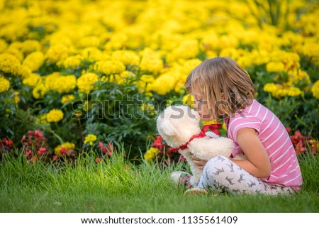 Adorable toddler girl kissing her favourite teddy bear in summer park on beautiful sunny day with yellow flowers in the background