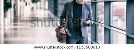 Business man texting on mobile phone commuting walking in airport with messenger bag using cellphone texting sms message on smartphone app - young businessman commute lifestyle panoramic banner. #1135600613