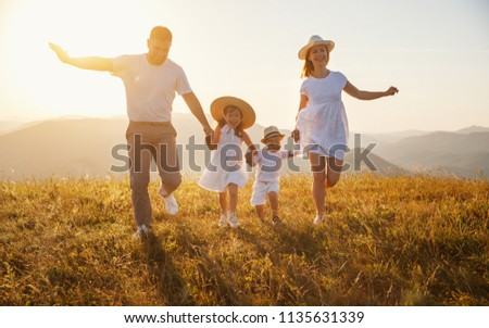 Happy family: mother, father, children son and  daughter on nature  on sunset #1135631339