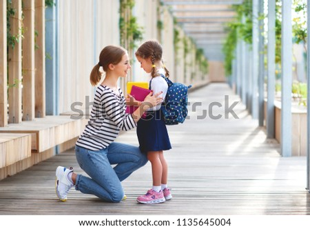 first day at school. mother leads a little child school girl in first grade #1135645004