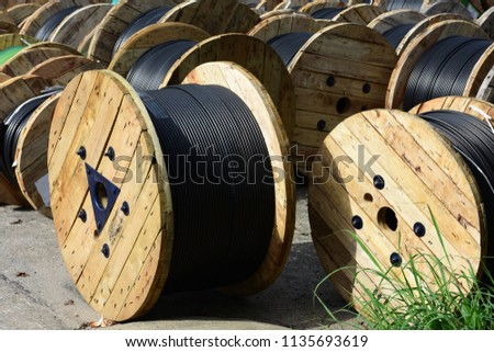 Wooden Coils Of Electric Cable Outdoor. High and low voltage cables in the storage. #1135693619