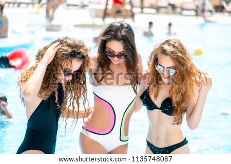 Attractive girlfriends with positive expression, demonstrates perfect body in swimsuits, getting sun bathes on beach,spending a good time in company of friends in tropical country. #1135748087