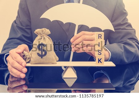 Financial risk assessment / portfolio risk management and protection concept : Businessman holds a white umbrella, protects a dollar bag on basic balance scale, defends money from being cheat or fraud #1135785197
