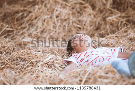 Cute asian child girl lying down on hay and play with hay stack in the farm with happiness