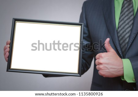 Blank diploma or certificate mock up in businessman hand. Empty photo frame border with copy space. #1135800926