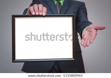 Blank diploma or certificate mock up in businessman hand. Empty photo frame border with copy space. #1135800965
