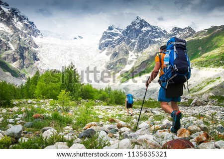 Climbers with hiking backpacks go to the mountain. hikers in mountains. Tourists hike on rocky mounts. Leisure activity on mountain trek in wild Svaneti region of Georgia. Groupe Hiking. Royalty-Free Stock Photo #1135835321