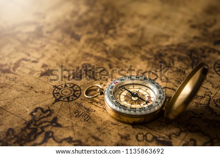 Old gold compass on ancient map background ,vintage tone with copy space for text. Royalty-Free Stock Photo #1135863692