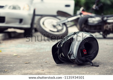 Close-up of a helmet of a driver with a blurred motorbike and car in the background Royalty-Free Stock Photo #1135934501