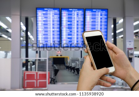 Mock up image. Woman, traveler using smart mobile phone making online check-in with abstract blurred flight schedule board at the international airport to travel on weekends. Royalty-Free Stock Photo #1135938920