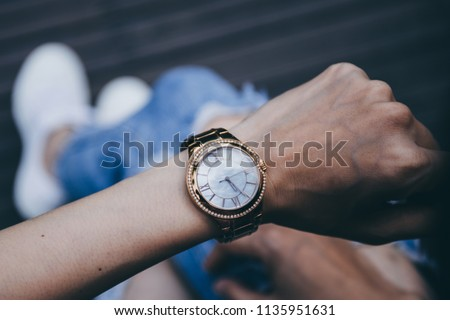 soft focus women in jean,white sneaker sitting outdoor on wooden floor background.looking at watch on hand, watching time. concept for punctuality, appointment Royalty-Free Stock Photo #1135951631