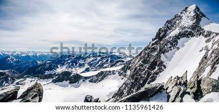 View of the highest austrian mountain Grossglockner. An alpine mountain landscape of High Taura with the summit of Grossgloner. Alpinist ascent route to the summit. Snow, rocks and sharp ridge. Royalty-Free Stock Photo #1135961426