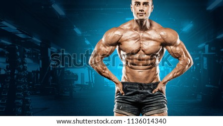 Brutal strong muscular bodybuilder athletic man pumping up muscles on gym background. Workout bodybuilding concept. Copy space for sport nutrition ads. #1136014340