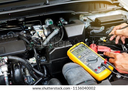 Car mechanic is using a multimeter with voltage range measurement to check the voltage level of the car battery.  #1136040002