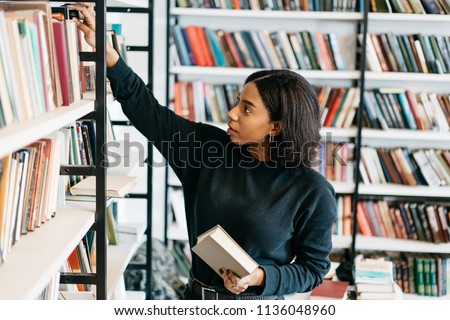 Young female african american librarian making order on bookshelves in college, dark skinned woman student picking literature for education checking information in books store, hipster girl get novels #1136048960