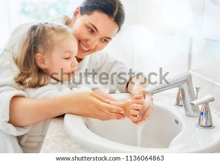 Cute little girl and her mother are washing hands under running water. Royalty-Free Stock Photo #1136064863
