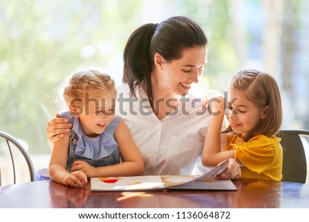 happy loving family. pretty young mother reading a book to her daughters #1136064872