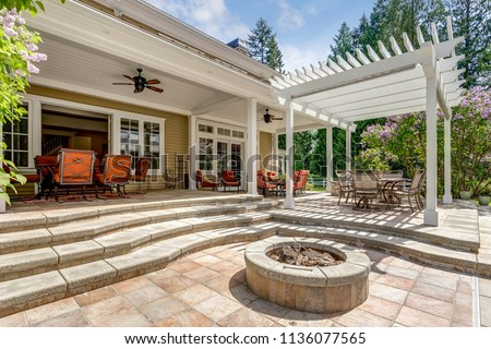 Lovely outdoor deck patio space with white pergola, fire pit in the backyard of a luxury house. #1136077565