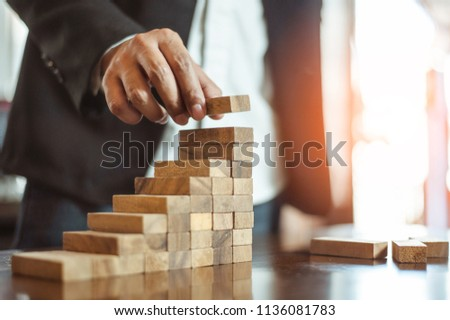 plan and strategy in business.risk concept.hand of man has piling up and stacking a wooden block.Businessman Building The Success. Royalty-Free Stock Photo #1136081783