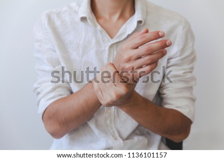 Closeup of male arms holding his painful wrist caused by prolonged work on the computer, laptop.Carpal tunnel syndrome, arthritis, neurological disease concept. Numbness of the hand