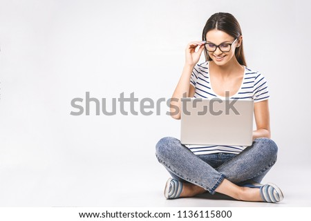 Business concept. Portrait of happy woman in casual sitting on floor in lotus pose and holding laptop isolated over white background.  #1136115800
