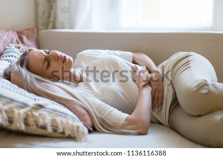 Health issues problems.Young Caucasian woman suffering from stomach pain, feeling abdominal pain or cramps, lying on sofa.Period menstruation, female health problem, aching belly and gynecology Royalty-Free Stock Photo #1136116388