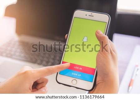 CHIANG MAI,THAILAND - JUL 11, 2018 : Hands using smart phone showing Snapchat app.Snapchat is a multimedia messaging app. #1136179664