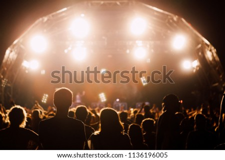 Crowd of people at the warm stage lights of summer music festival #1136196005