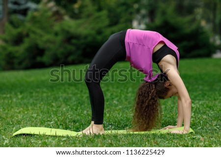 young beautiful woman doing stretching exercises in summer park. #1136225429