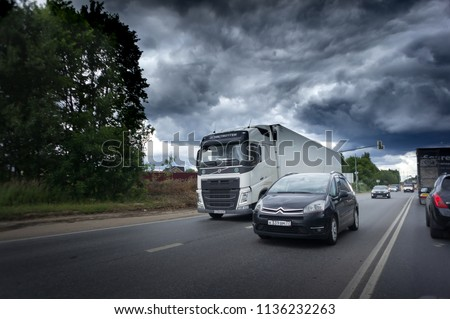 Russia, Moscow. 17 JULY 2018. New Riga highway. Black car and truck with container on road, cargo transportation and shipping concept. Storm clouds #1136232263