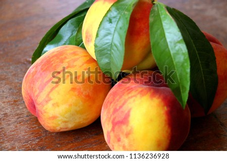 Peach fruit with leaf  on a wooden background. #1136236928