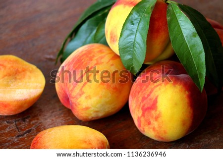 Peach fruit with leaf  on a wooden background. #1136236946